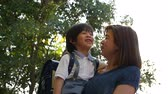 notas : Asian mother holding her son while walking in the park , back to school concept slow motion