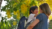 grade : Asian mother holding her son while walking in the park , back to school concept slow motion