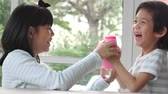 cofrinho : Cute Asian child putting a coin in to a piggy bank slow motion Vídeos