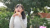 fastfood : Beautiful Asian girl eating eating pizza outdoor slow motion
