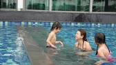 à beira da piscina : Asian Mother and children playing in swimming pool slow motion