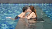 à beira da piscina : Asian Mother and son playing in swimming pool slow motion