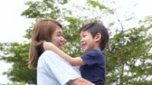 piggyback : Asian mother carry herson in the park on summer day slow motion Stock Footage