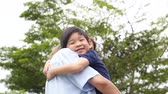 coréia : Asian mother carry herson in the park on summer day slow motion Vídeos