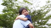 omini : Asian mother carry herson in the park on summer day slow motion Filmati Stock