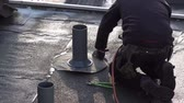 dekarz : Moers  Germany - February 01 2018 : Roofer installing chimney using bitumen and gas flame Wideo