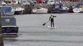 yatılı : Caernarfon  Wales - May 01 2018 : Man stand up paddling in the harbour
