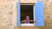 provence : Woman opening the shutters Stock Footage