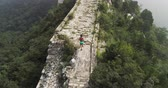 parede de tijolos : Young woman running on great wall