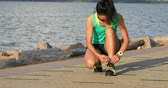 aparando : Healthy lifestyle fitness woman runner tying shoelace before running on sunny seaside