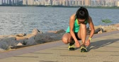 tkanička : Healthy lifestyle fitness woman runner tying shoelace before running on sunny seaside
