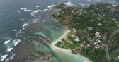 Aerial view.Drone ascent aerial footage of ocean waves and fishermen village landscape