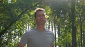 heart beat : Portrait of an Athletic caucasian sportsmen running through the woods. Jogging in forest concept. Stock Footage