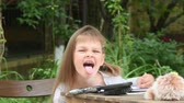 inculto : Girl sits at a table in the courtyard and grimacing showing tongue to the frame Vídeos