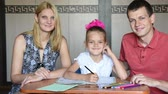 velo : Schoolgirl doing homework with their parents smile looked into the frame
