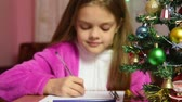 ostrý : Girl writing a letter to Santa Claus, the focus is on the fur-tree in front of her Dostupné videozáznamy