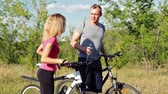 Attractive couple walking with bicycles and drinking water in the forest