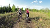 Cyclists riding on bikes and speaking with each other in the forest Wideo
