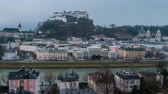 подсветкой : View of Salzburg, Austria at night. Illuminated Castle at the background, reflection in the river. Dark fast pacing sky, time-lapse
