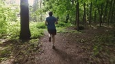 adult : Adult man running jogging outdoors in a forest nature on a forest trail and enjoying it and looking happy
