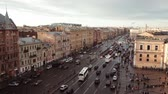 People and cars moving along prospect in Saint Petersburg at evening