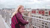 Frozen woman in leather jacket feel cold while standing on the roof in the wind