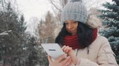 chvět se : Young cute girl in winter park uses tablet pc