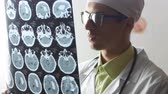 ischemic : A neurosurgeon doctor looks at a Magnetic resonance imaging MRI snapshot of the brain Stock Footage