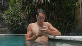 sloppy : Young man talking on the phone in the pool Falls smartphone in water. Sloppy man is missing a smartphone in the pool water