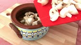 Preparing meal with meat and mushrooms into traditional Bulgarian gyuvetche clay pot