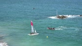 engels : Saint-Malo  Ile-et-Vilaine - 19 August, 2019: young sailors training on the beach of Saint-Malo and launching racing catamarans into rough seas Stockvideo