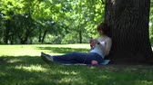crocheting : young girl doing knitting in the park under a tree