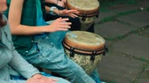 djembe : Young white girl playing Bongo drum with friends close up