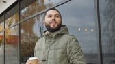 mulled : Handsome young bearded man is holding a cup. drinking hot drink coffee or tea in autumn outdoors