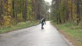 patenci : Man riding on a longboard skate on a road through a forest