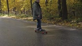 kaykay : Man riding on a longboard skate on a road through a forest