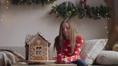 perník : Beautiful woman wearing winter outfit drinking tea with gingerbread at home near Christmas tree Dostupné videozáznamy