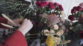 arranjando : Master class of female florist at work with bunch of flowers. Girl making bouquet of various autumn flowers. Business woman florist at flower shop