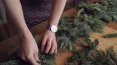 Florist at work: woman hands making christmas decorations garland of fir Nobilis. Happy new year dinner feast