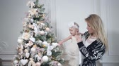 Happy mother and daughter embracing. White wall and decorated tree on background. Christmas or New year celebration.