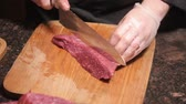 rzeźnik : Chef cuts meat on wooden cut board. Fresh raw meat in restaurant. Selective focus.