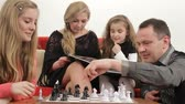sister : Father playing chess with his senior daughter and mother reading a book with the junior