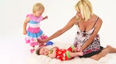 vinha : Footage of a happy young fair haired mother sitting with two children - toddler and baby. Baby boy is lying on the plaid on the floor, baby girl came up to a woman to sit down. Studio shot on white background. Vídeos