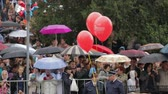 sevastopol : SEVASTOPOL, REPUBLIC OF CRIMEA - MAY 9, 2014: Dolly shot of crowds of people with umbrellas gathering at the main street and waiting for the parade devoted to anniversary of Victory Day on May, 9 in Sevastopol.