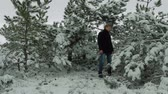 forest : Young man is singing with emotions with trees covered with snow on winter forest background.