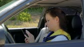 delighted : woman sits behind the wheel of a car and uses a smartphone