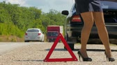 внимание : a woman walks next to a warning triangle