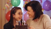 making a wish : Happy mother and daughter blowing candles of birthday cake Stock Footage