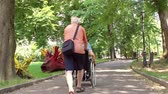 Senior man walking with disabled young man in wheelchair in the park. Wideo