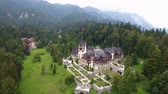 first : Peles Castle in forest 6. Aerial shot of Peles Castle in forest, Transylvania, Romania. Tourists visit the Peles castle, a masterpiece of Neo-Renaissance style, built between 1873 and 1914, the first European castle entirely lit by electrical current. Stock Footage